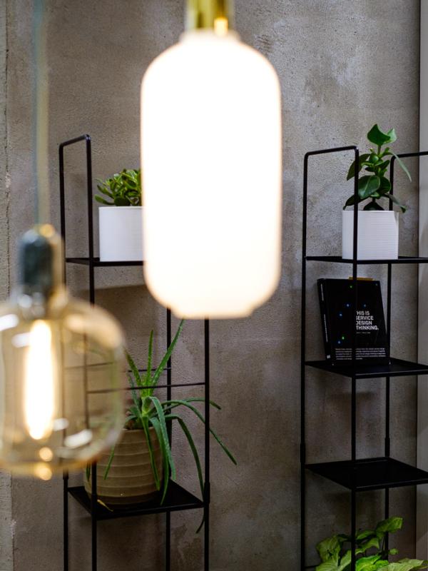 Normann Copenhagen Amp Lamp -valvaisimia betoniseinän ja hyllyjen edessä.