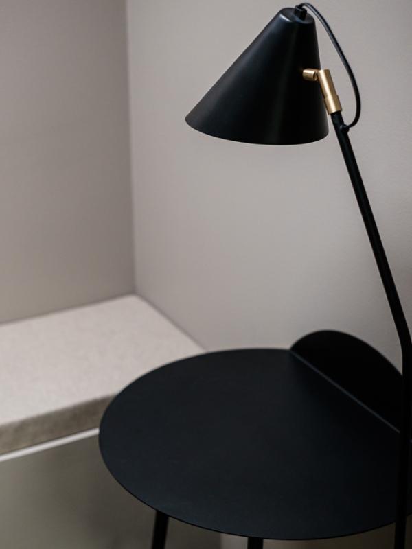 Lähikuva puhelinkopin valaisimesta ja pöydästä.