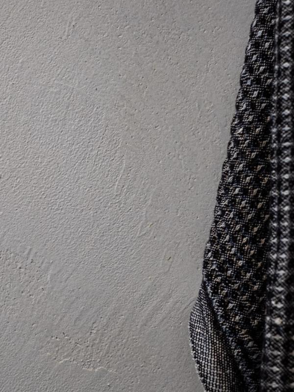 Betonia ja rouheaa kangasta osana sisustussuunnittelua.