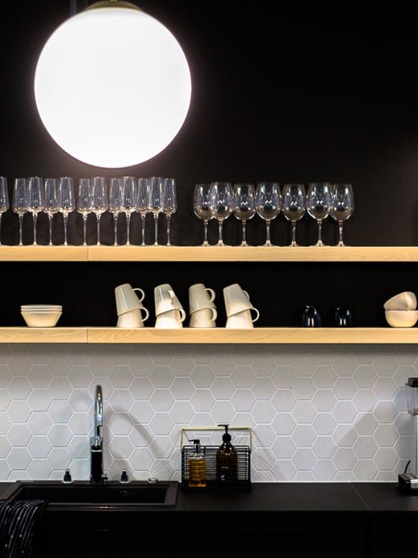 Avaran keittiön avohyllyillä viinilaseja ja kahvikuppeja.