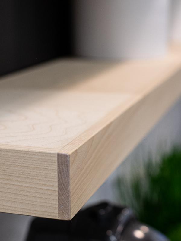 Puuhyllyn tekstuurit ovat näkyvissä hyllyissä.