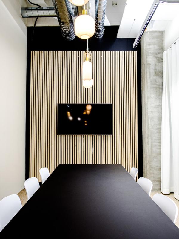 Musta, valkoinen, betoni ja Suomalainen koivu neuvottelutilan sisustuksen teemoina.