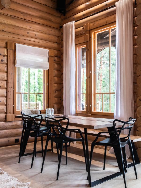 Pöydän mustat metallijalat ja mustat tuolit luovat nykyaikaista särmää hirren pariksi.