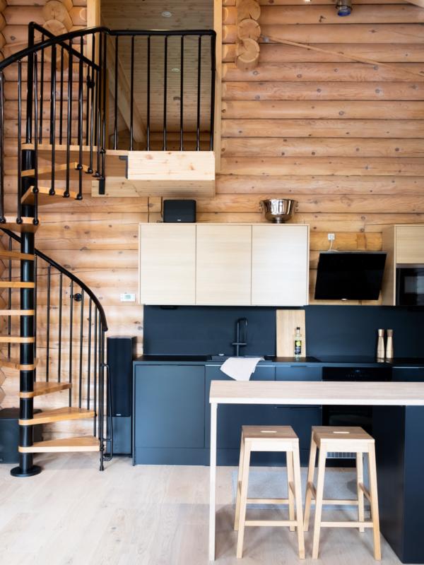 Hirsihuvilan kierreportaat ja moderni keittiö ovat pääosassa tilan sisustussuunnittelussa.