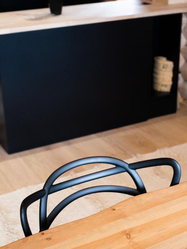 Pöytälevyn aaltoilevat reunat ja tuolin selkänoja.
