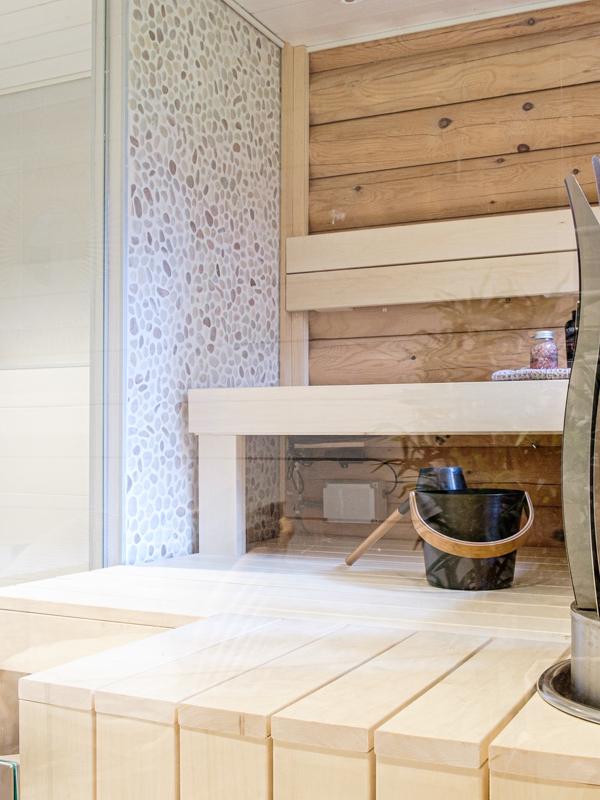 Sauna ja suihku on erotettu lasiseinällä.