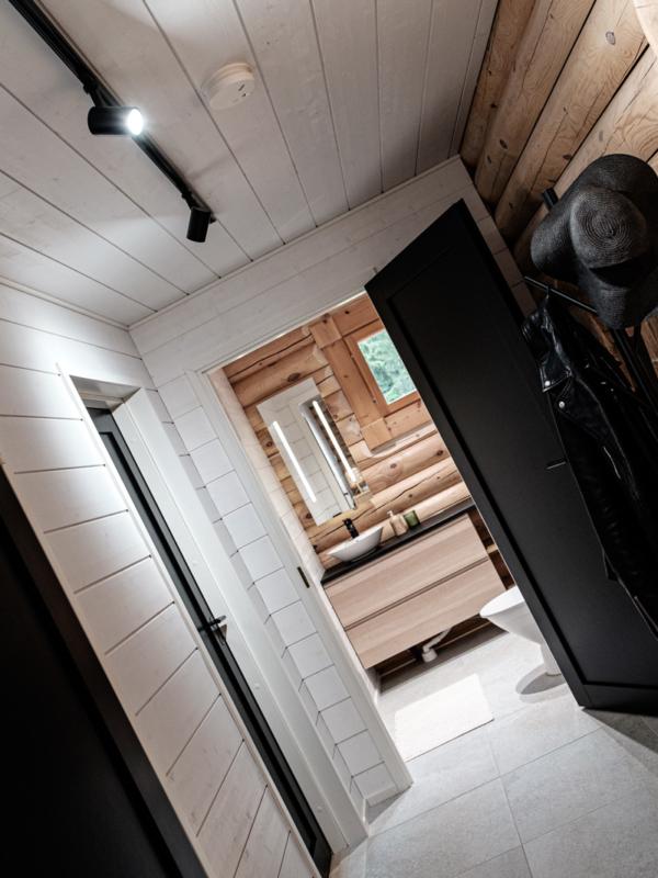 Mustat raidemaiset led-spotit löytyvät myös aulasta. Huomaa myös mustat ovet ja ovenkahvat.