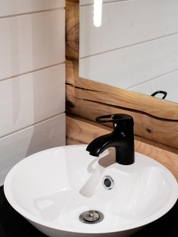 Myös WC:n lavuaarin hana on mustaa metallia. Peilissä on upotetut valaisimet.