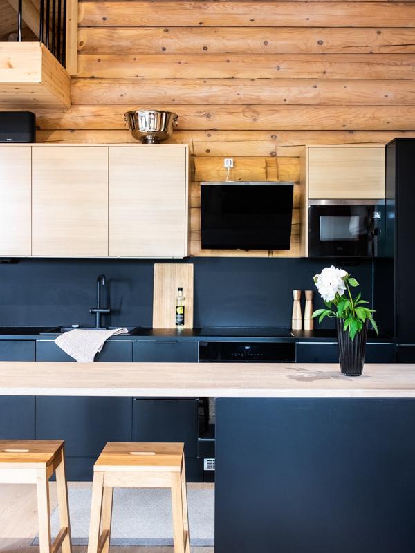Hirsihuvilan moderni keittiö tuo tilaan kulmaa ja kontrastia.
