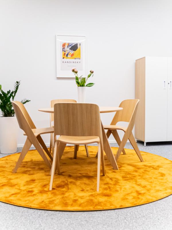 Toimistoon tuli värikäs pyöreä matto ja muotokieleen sopiva pöytä- ja tuoliryhmä.