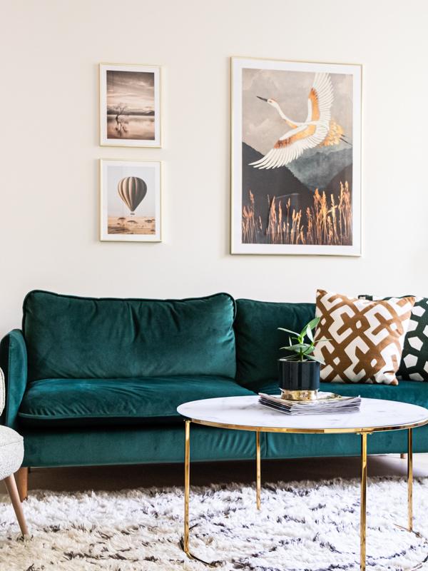Näkymä olohuoneeseen asunnon keittiöstä. Vihreä sohva tuo särmää sisustukseen.