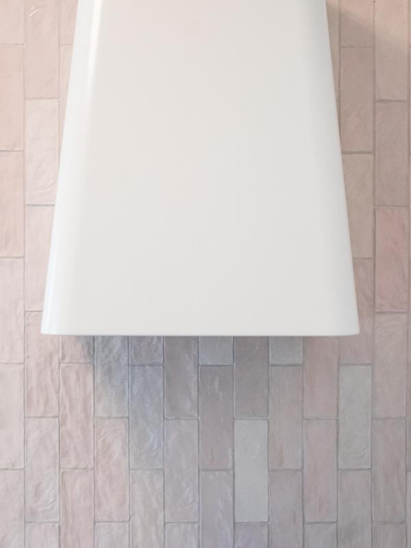 Keittiön tyylikäs, korkea liesituuletin korostaa pystysuuntaan asennettua laattaa.