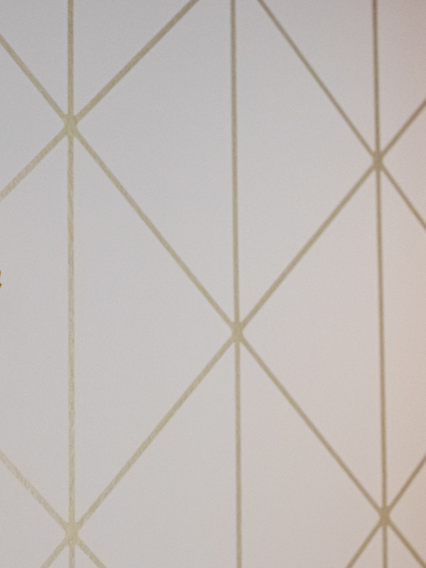 Moderni tapetti ja klassiset naulakot luovat yhdessä asunnon aksenttien kanssa etäisen Art deco -tunnelman.